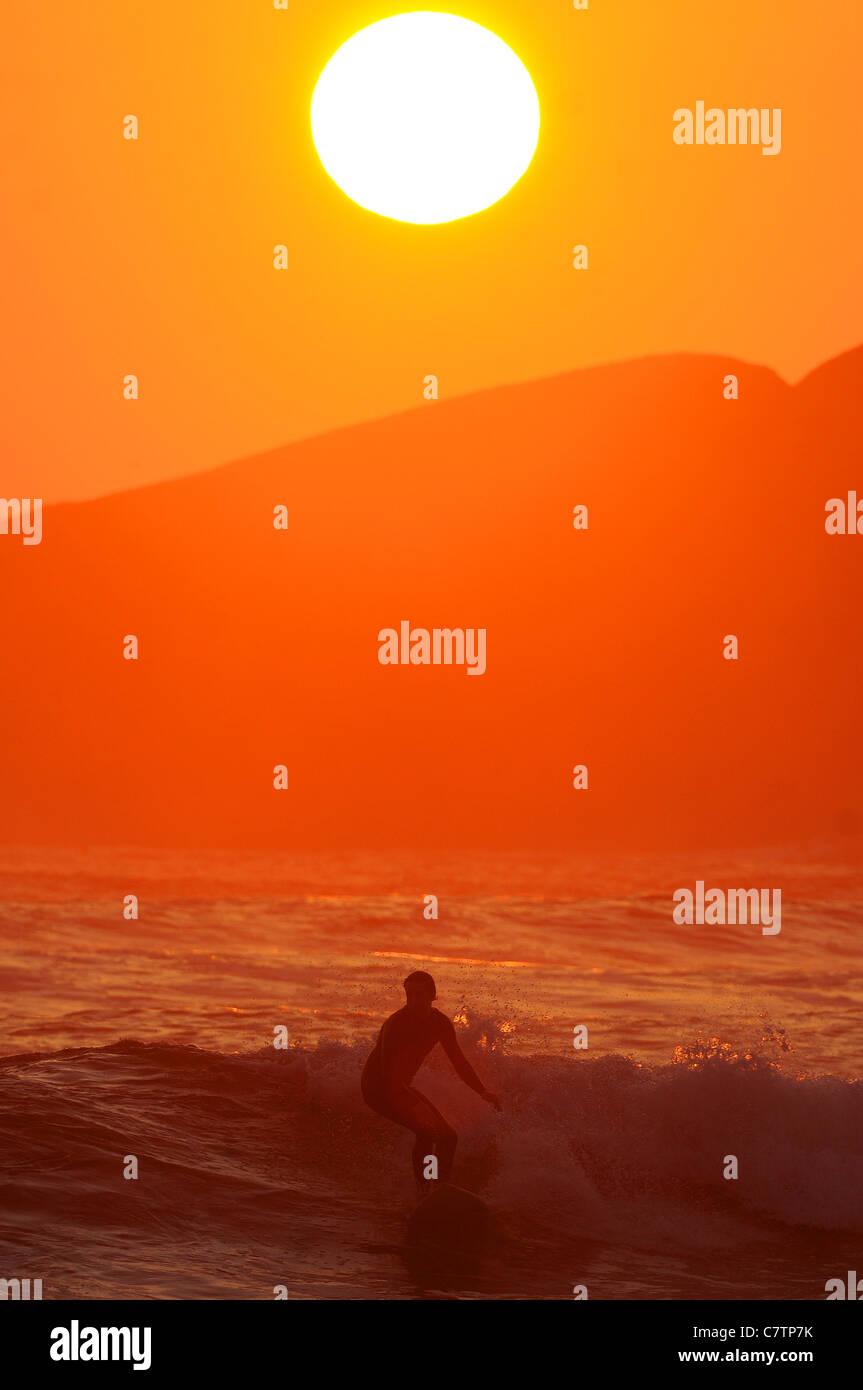 Eine Surfer reitet Wellen bei Sonnenuntergang Größe Strand in South Devon im späten September. Stockbild