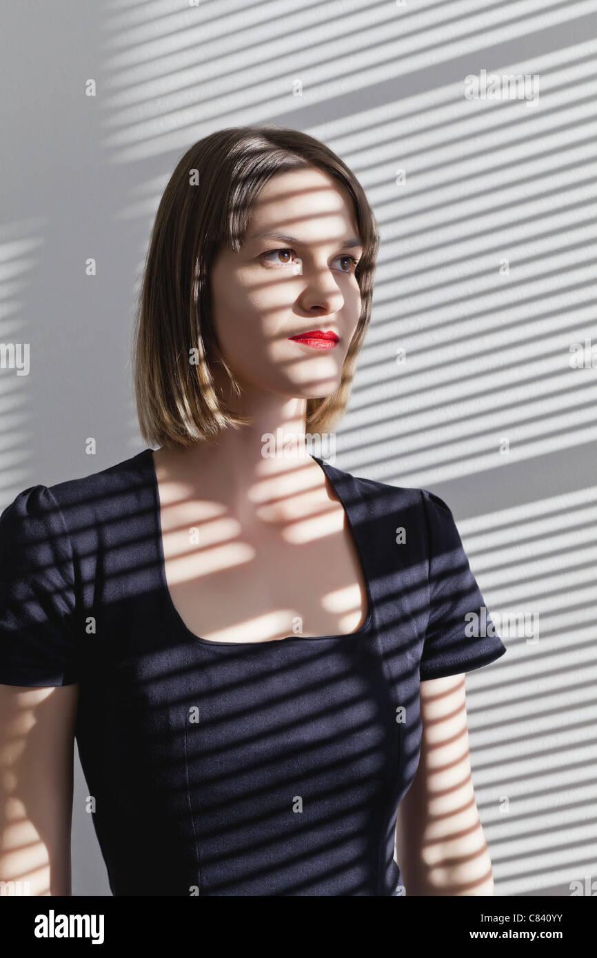 Frau im Schatten der Vorhänge Stockbild