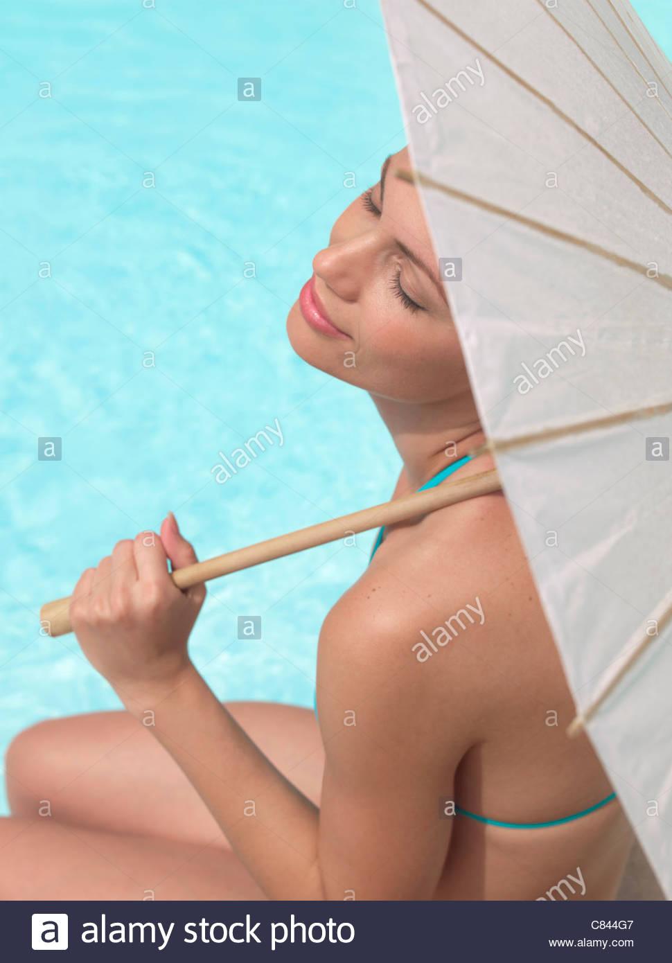 Frau sitzt Pool unter Dach Stockbild