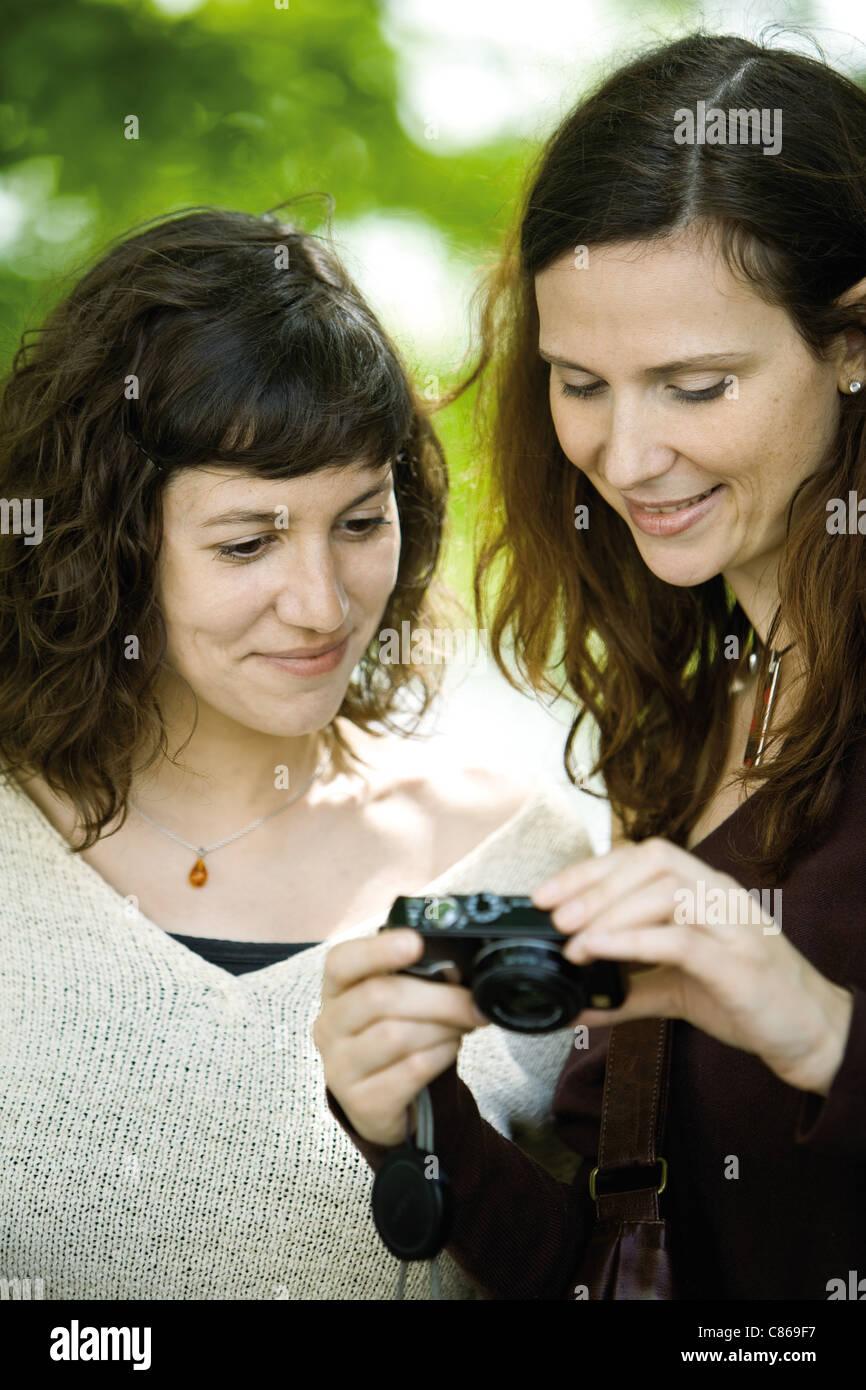 Frau zeigt Digitalkamera an Freund Stockbild