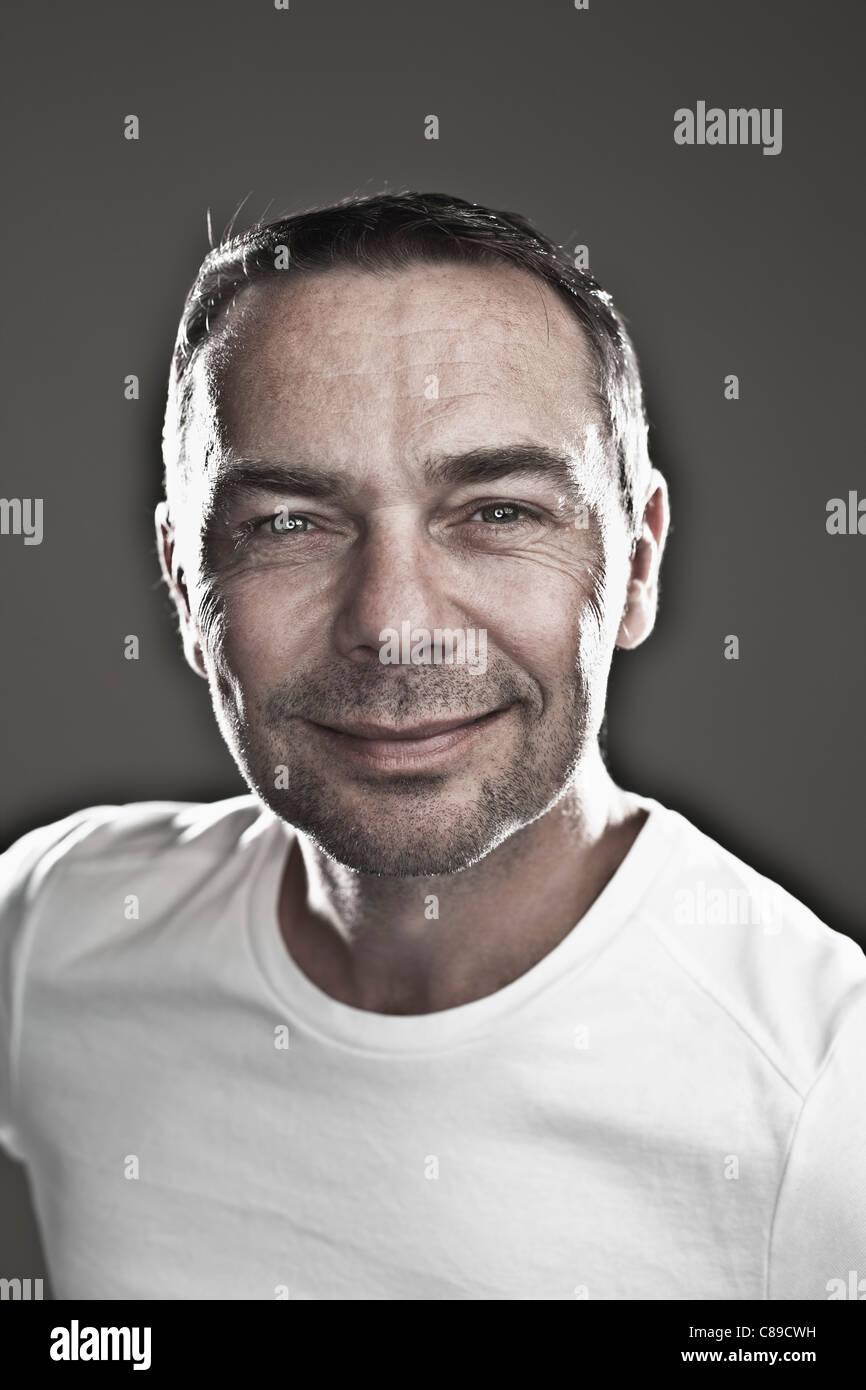 Nahaufnahme eines reifen Mannes vor schwarzem Hintergrund, Lächeln, Porträt Stockbild