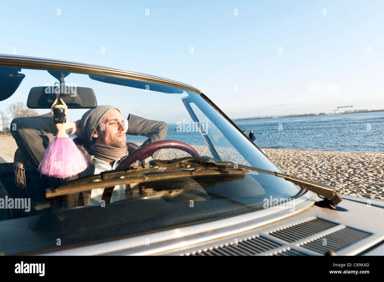 Deutschland, Hamburg, Mann sitzt im klassischen Cabriolet Auto in der Nähe von Elbe-riverside Stockbild