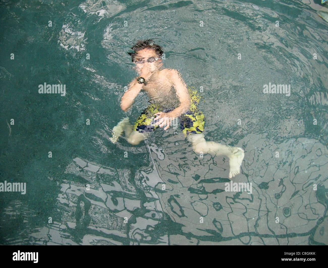 Ein kleiner Junge unter Wasser schwimmen Stockbild