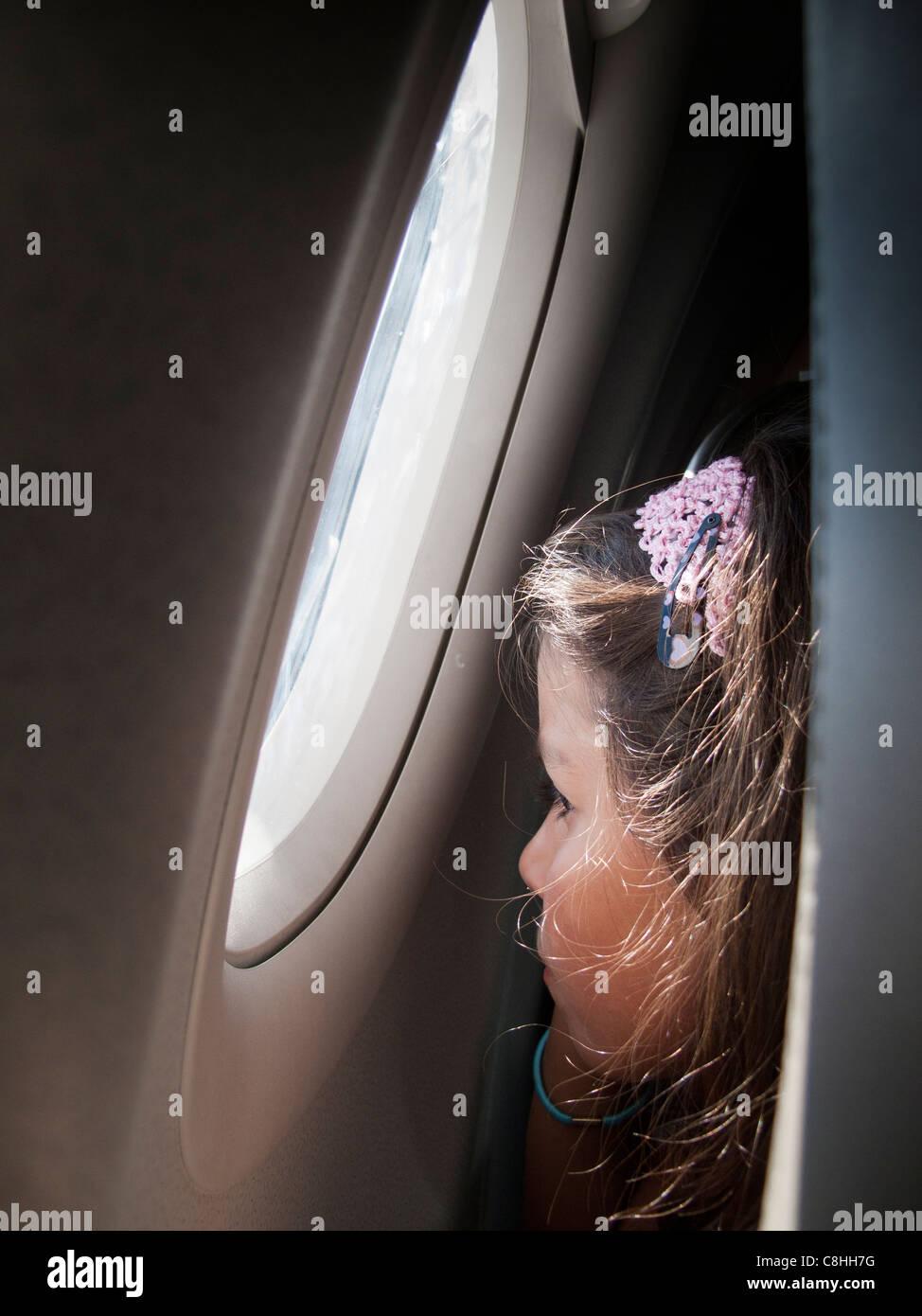 Kind schaut aus dem Fenster auf einem Flugzeug Stockbild