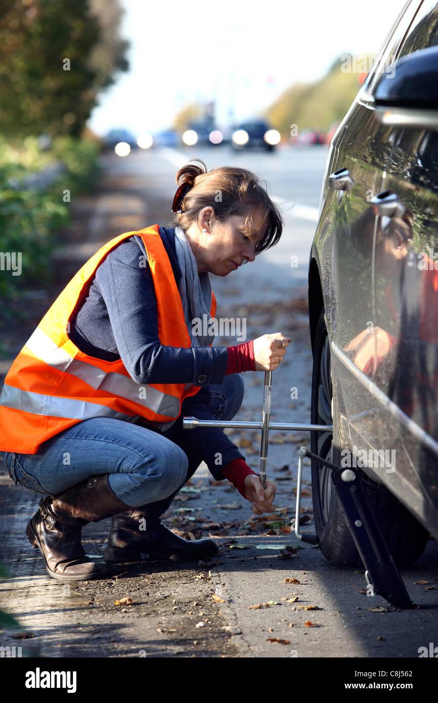 Panne, Platten Reifen. Frau ändert einen Reifen eines Autos auf einer Autobahn, eine Warnweste zu tragen. Stockbild