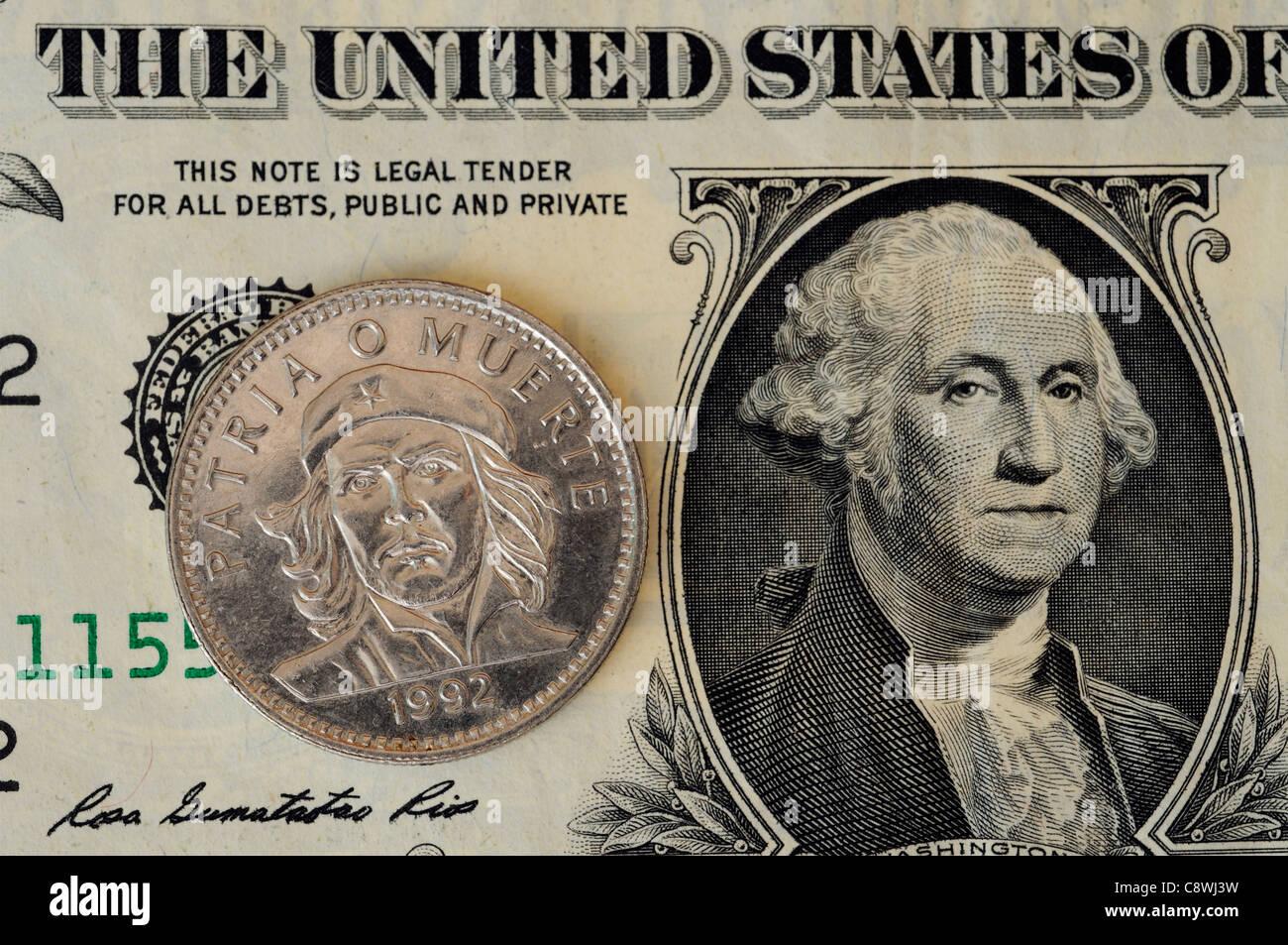 Eine kubanische Münze mit dem Porträt von Che Guevara und einem amerikanischen Dollarschein Stockbild