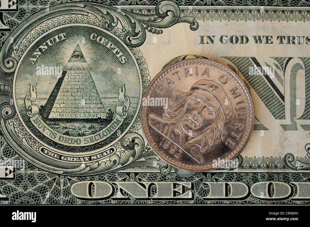 Eine kubanische Münze mit dem Porträt von Che Guevara und eine Pyramide auf dem amerikanischen Dollarschein Stockbild