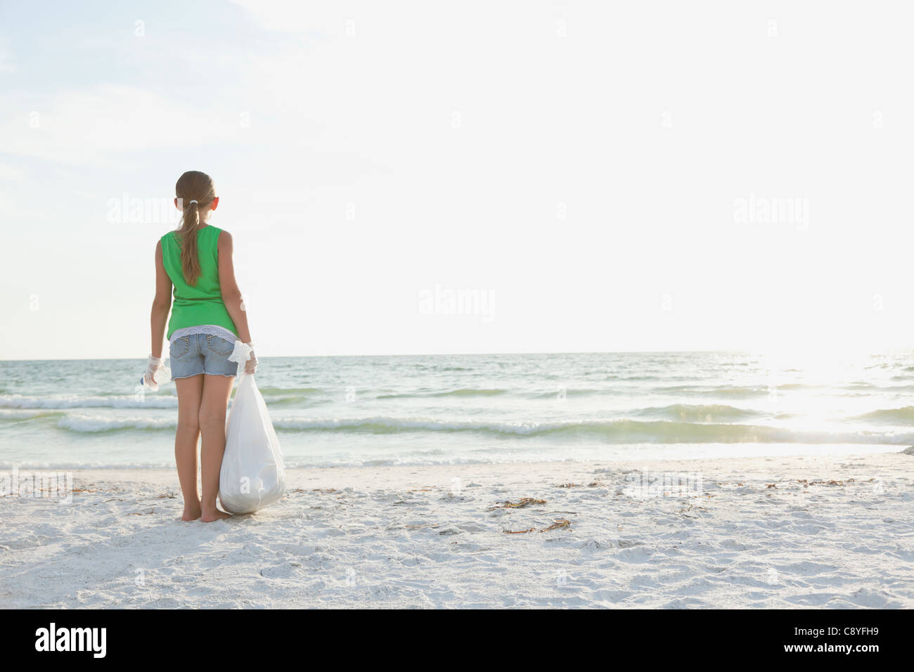 USA, Florida, St. Petersburg, Rückansicht des Mädchens (10-11) stehen am Strand mit Müllsack, mit Stockbild