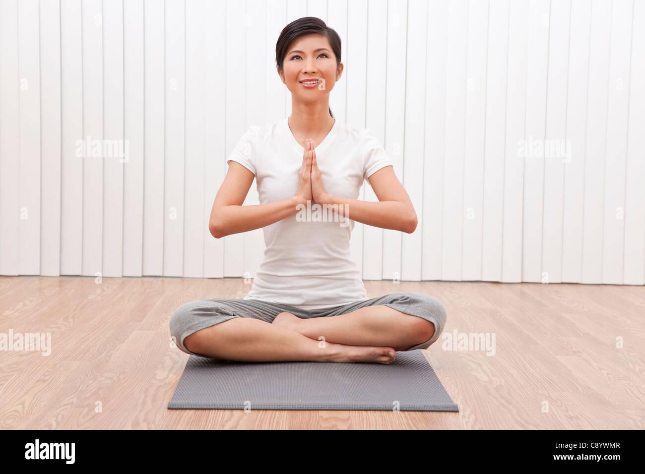 Eine schöne junge chinesische asiatische Oriental Frau Schneidersitz sitzen in einer Yogaposition in einem Stockbild