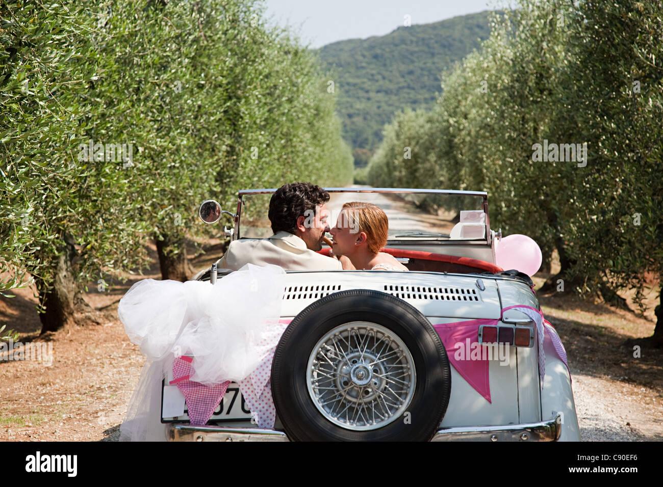 Brautpaar küssen im Oldtimer Stockbild