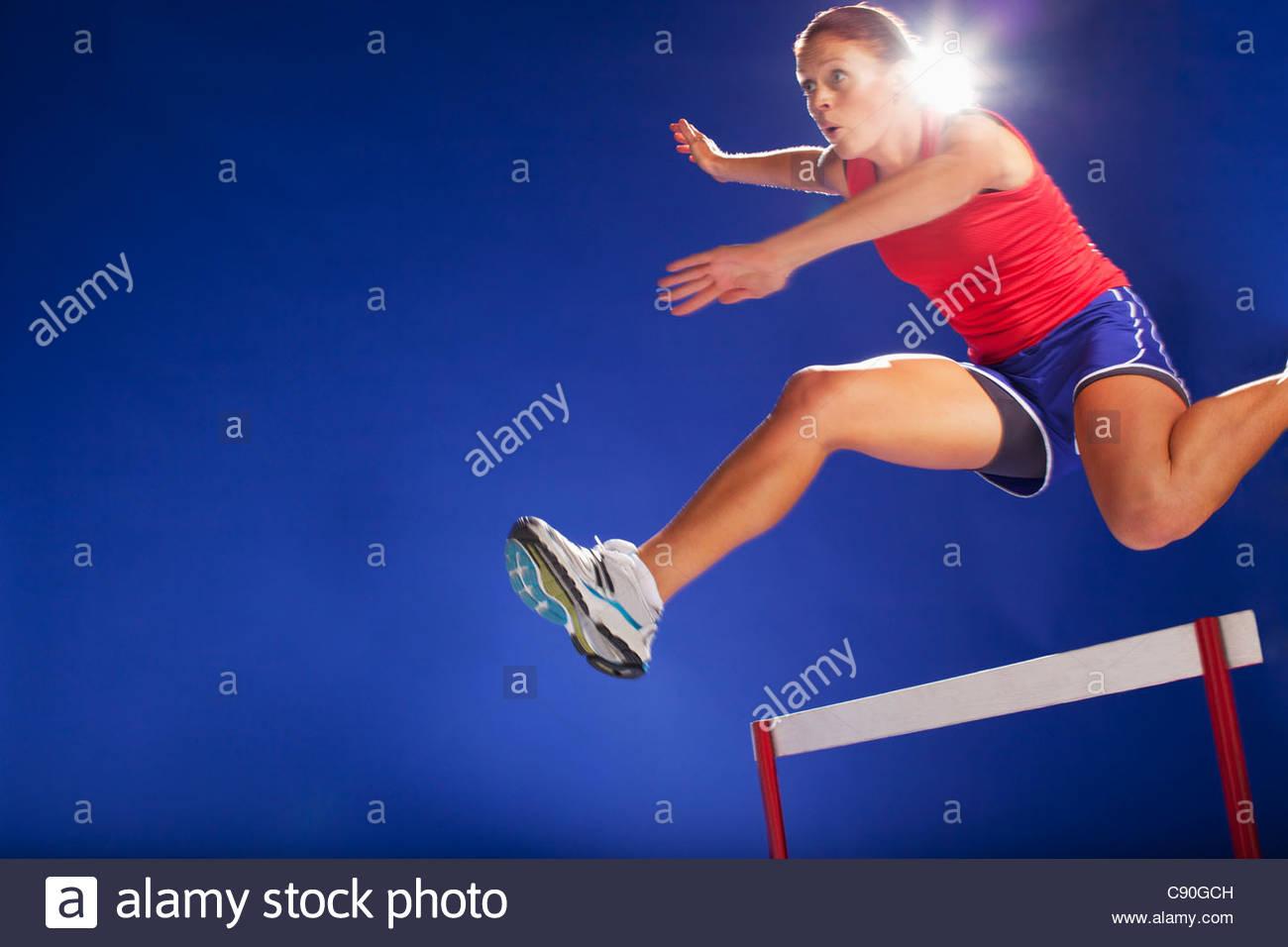 Sportler über Hürden zu springen Stockbild