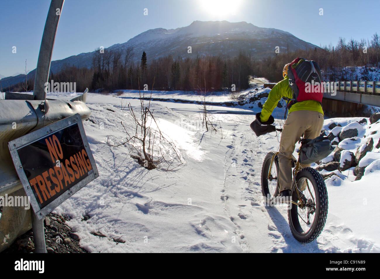 Mann Radfahren hinter einem No Trespassing Zeichen entlang der Knik River auf den Knik-Gletscher auf dem fetten Stockbild