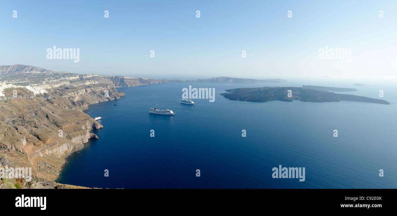 Panoramablick über die weiten Santorini Caldera mit Kreuzfahrtschiffen in seinem blauen Meer. Auf der linken Stockbild