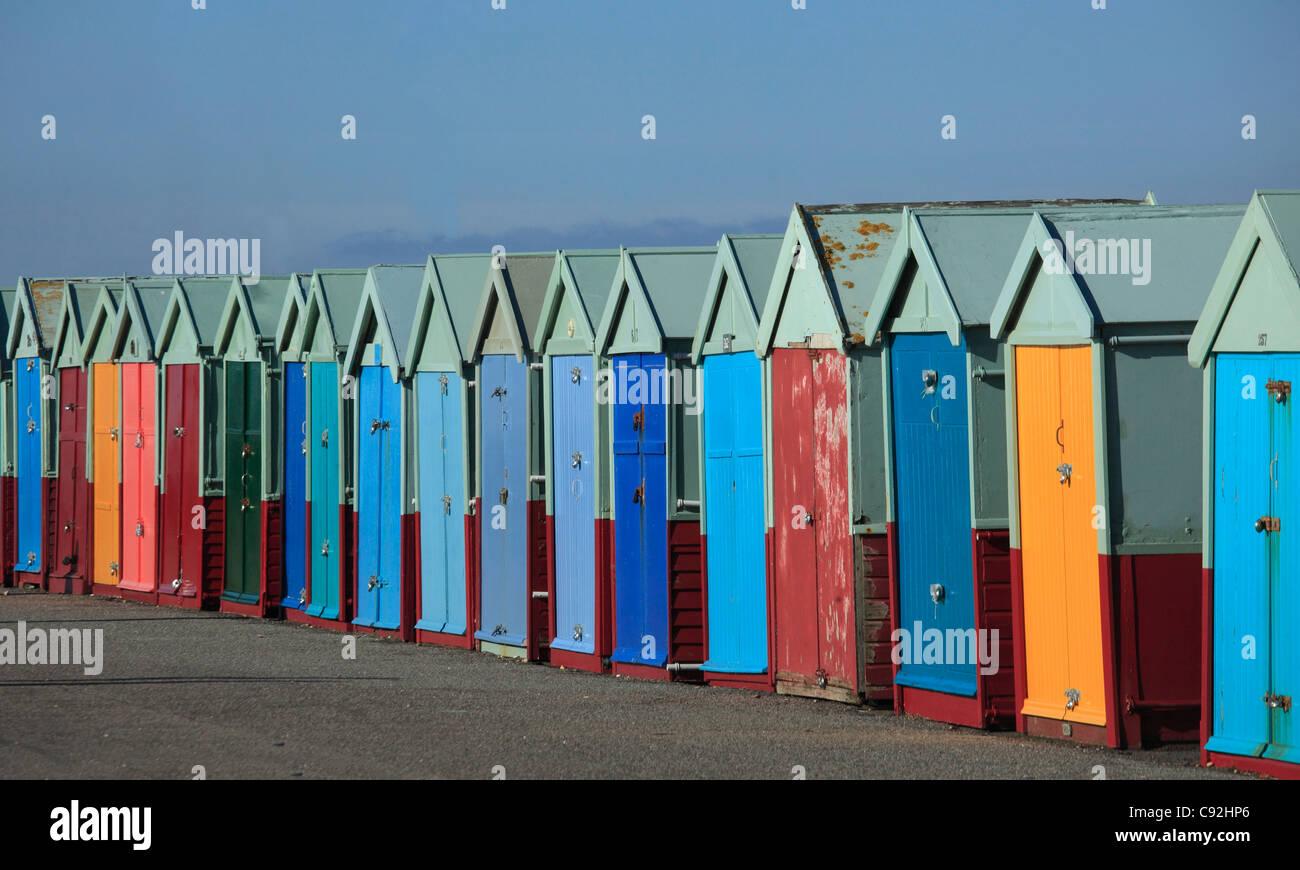 Brighton hat Reihen von bunten Strandhütten an der Strandpromenade. Die Türen sind helle Farben lackiert. Stockfoto