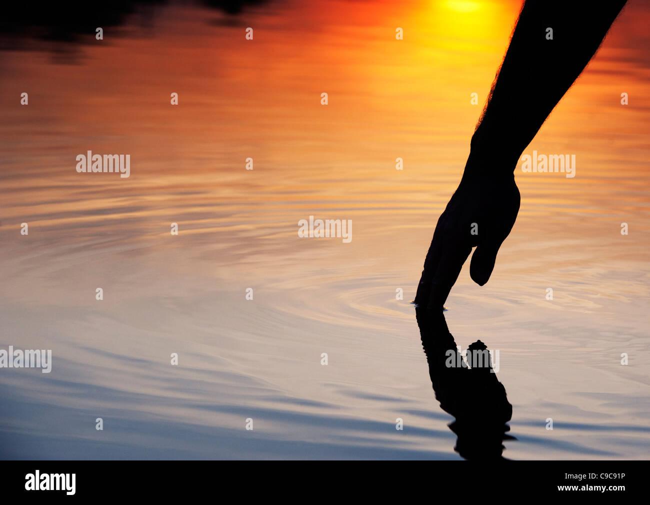 Hand berühren Wasser Welligkeit verursacht bei Sonnenaufgang Silhouette. Indien Stockbild