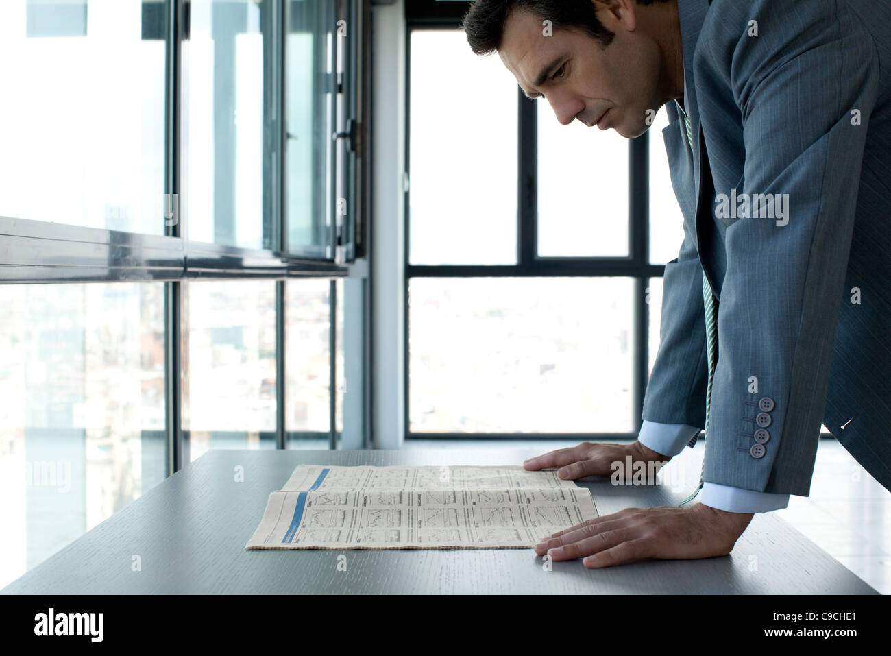 Geschäftsmann, die Finanzen der Zeitung zu lesen Stockbild