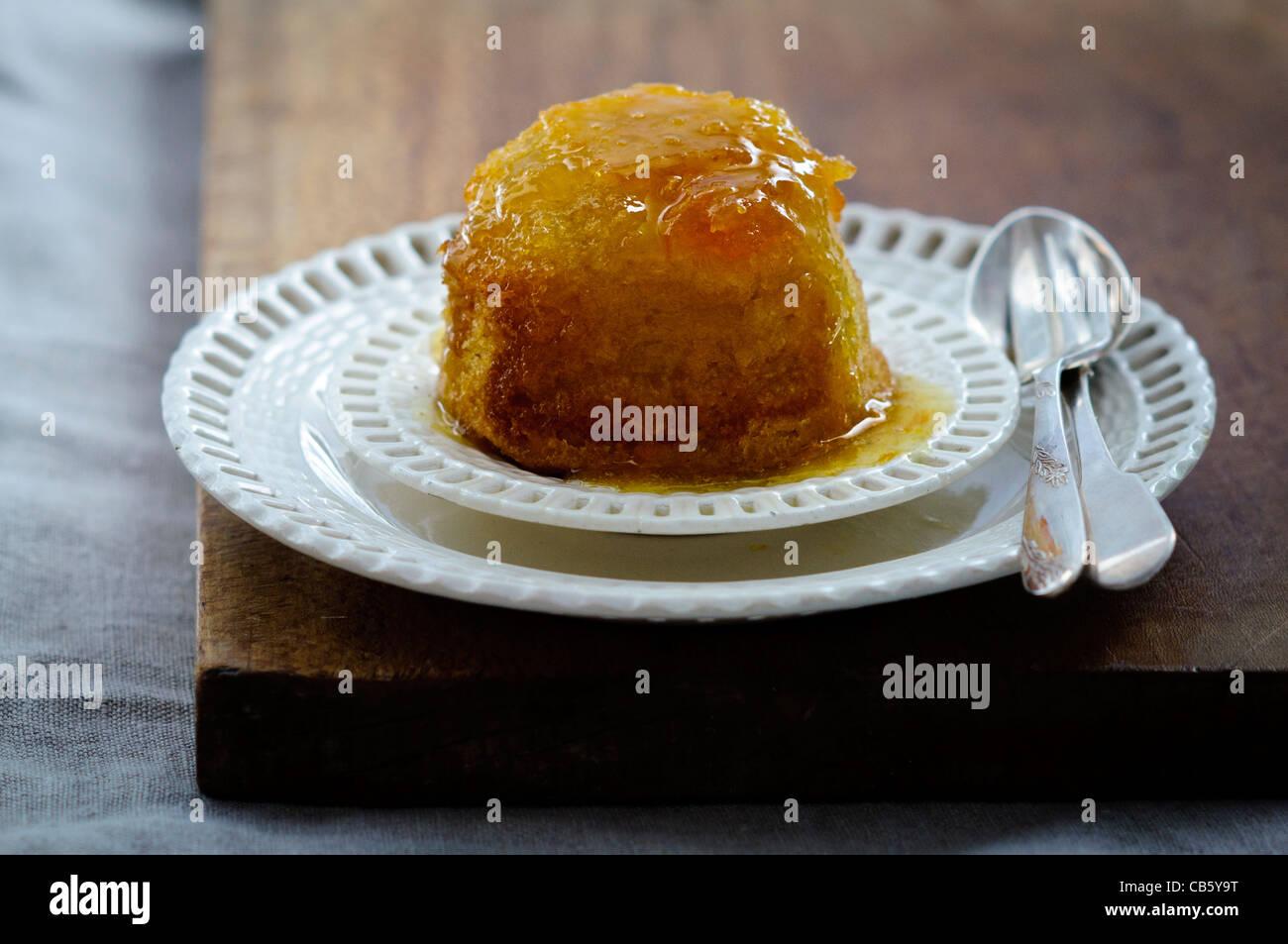 gerne St Clements Pudding auf Creme Band Platten mit Vintage Besteck. Stockbild