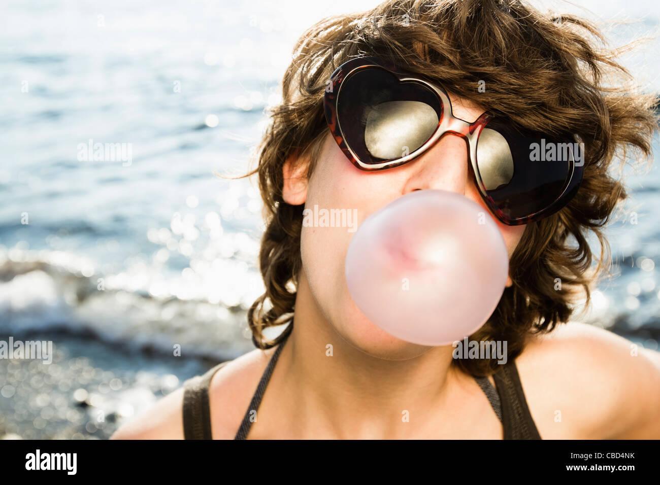 Frau bläst Blase am Strand Stockbild