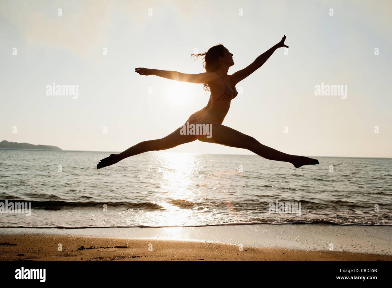 Frau springt über Wellen am Strand Stockbild