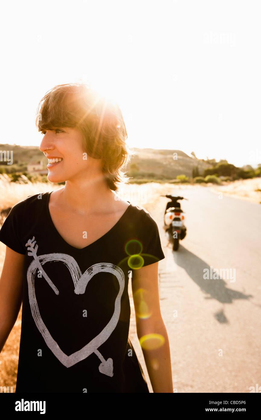 Lächelnde Frau zu Fuß auf Landstraße Stockbild