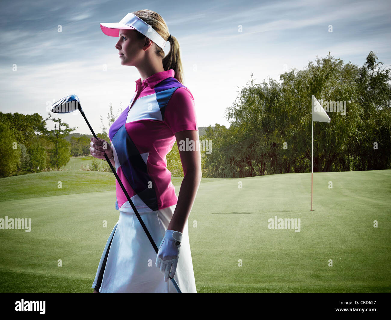 Frau mit Golfclub auf Kurs Stockbild