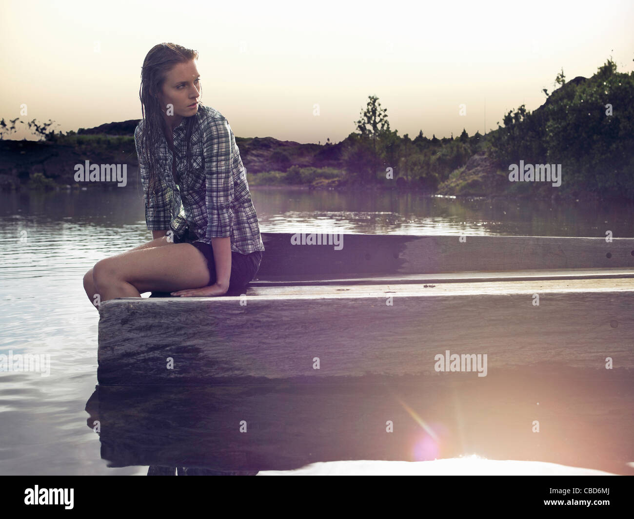 Frau sitzt auf dock-See Stockbild