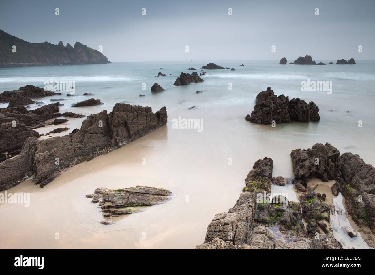 Wellen am felsigen Strand abwaschen Stockbild
