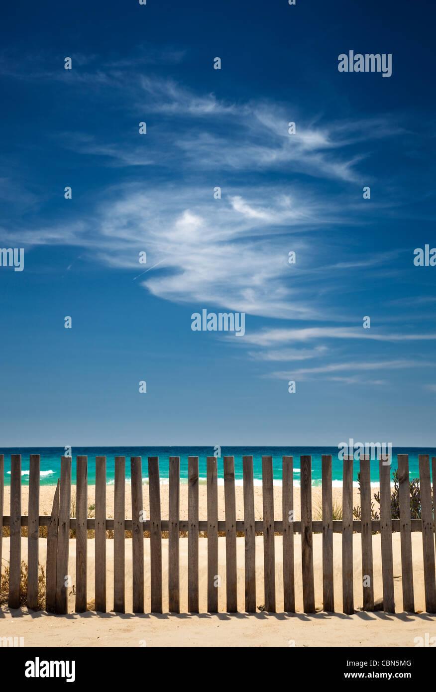 Himmel mit Wolken am Strand mit einem Holzzaun Stockbild