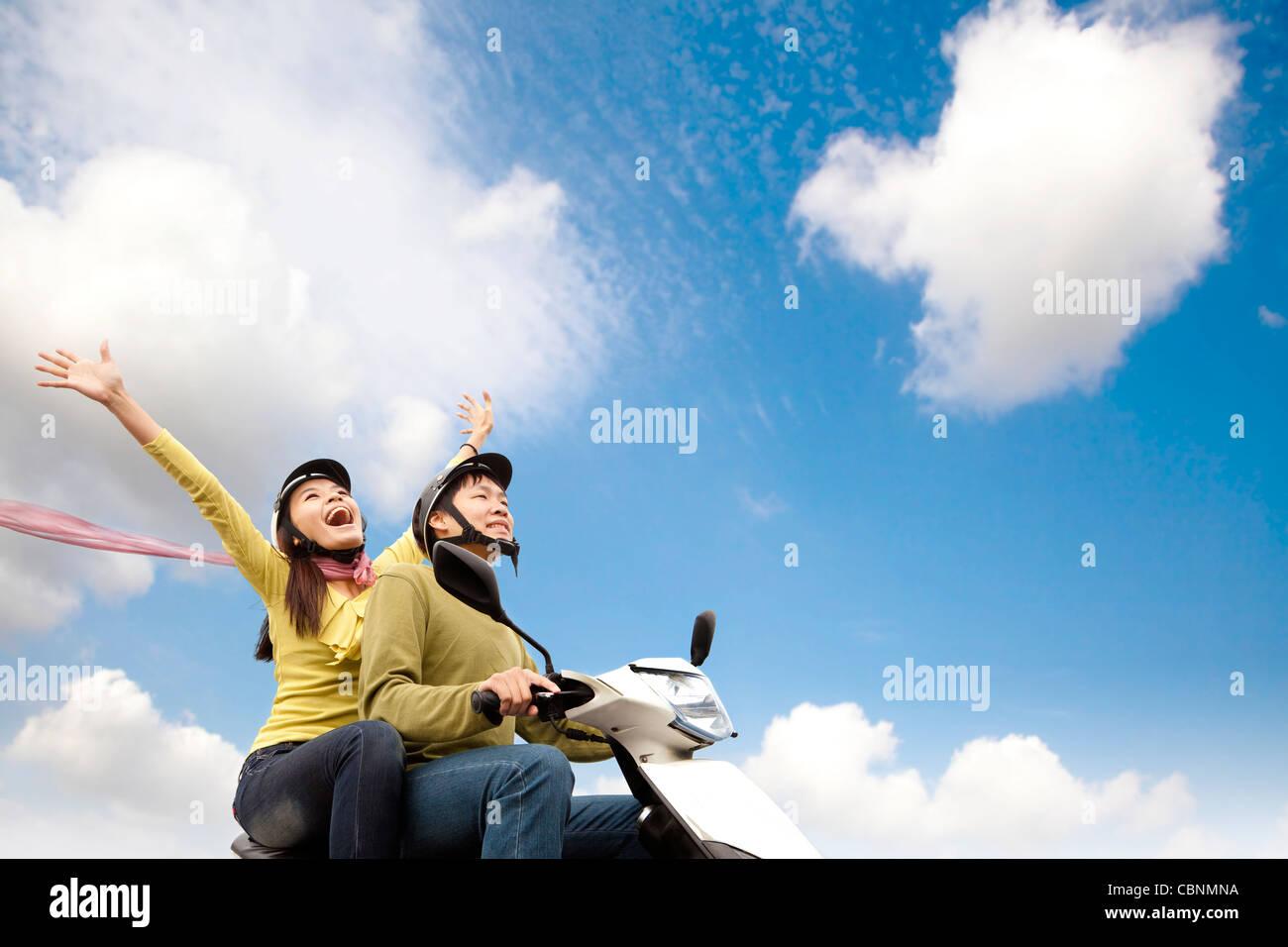Glückliche junge Paare, die Spaß auf einem Roller Stockfoto
