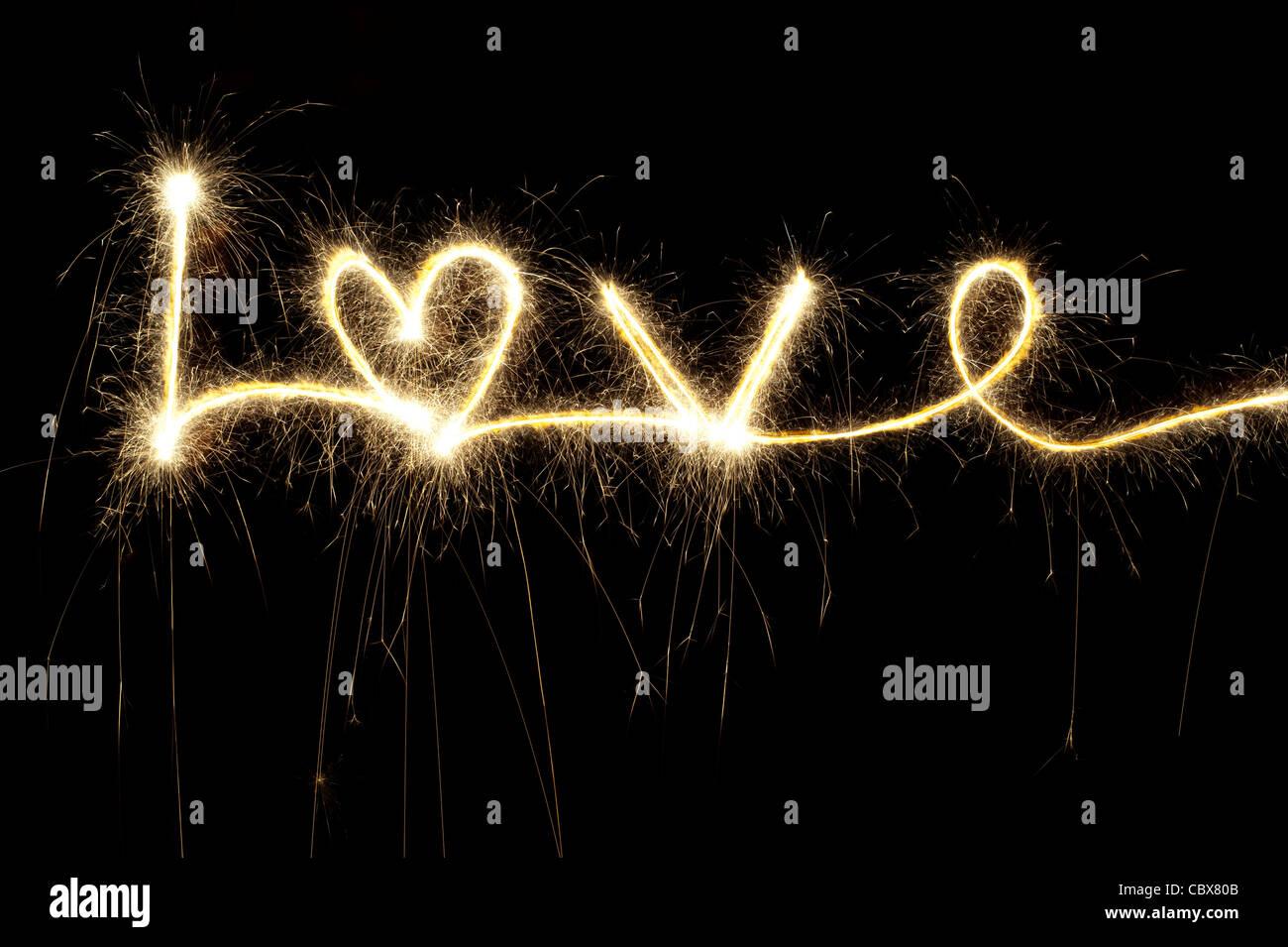 Liebe, geschrieben mit einer Wunderkerze in der Nacht einschließlich einer Herzform Stockfoto