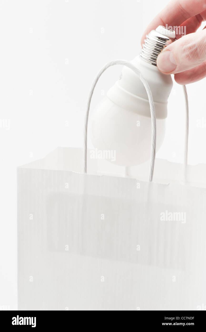 Hand, indem Energie effiziente Glühbirne in Papiertüte Stockbild
