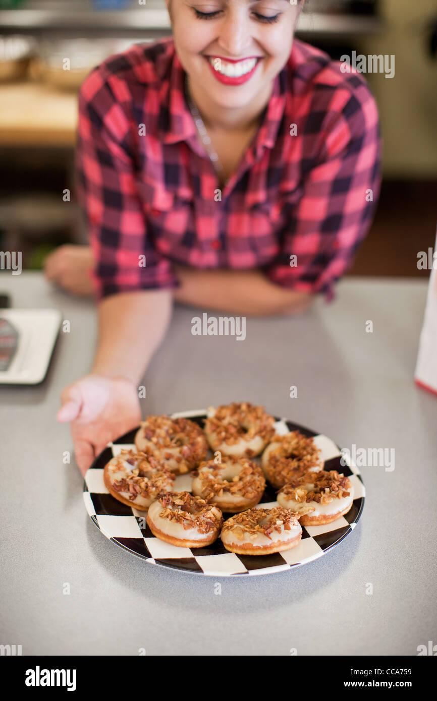 Junge Frau, die Halteplatte an frisch gebackenen Kuchen in der Bäckerei Stockbild