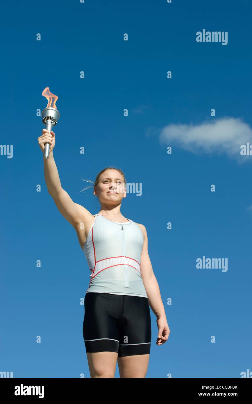 Sportlerin, die Fackel hochhält Stockbild