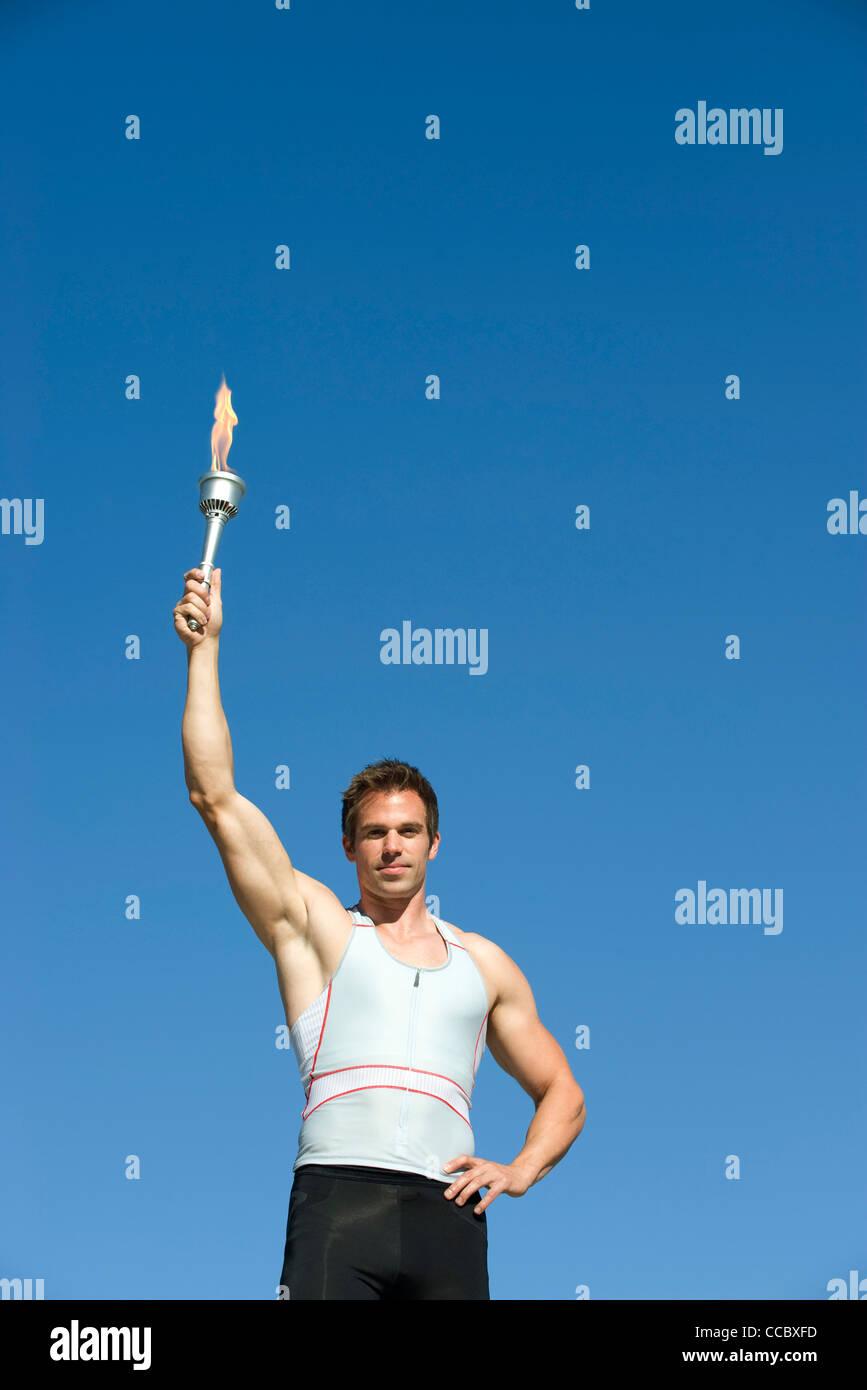 Männlicher Athlet hält Fackel Stockbild