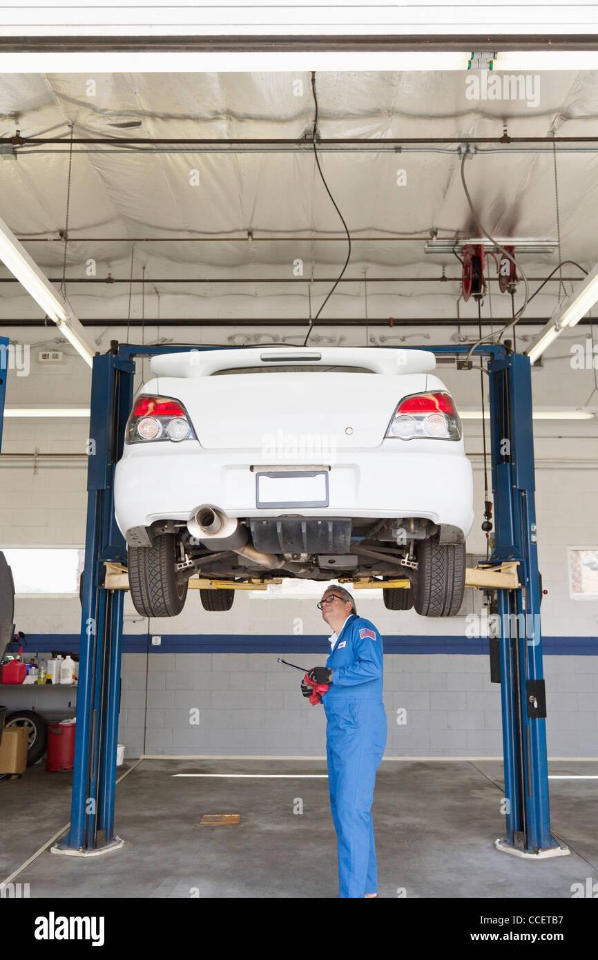 Mechaniker überprüfen unter Wagen auf einer Hebebühne Stockbild