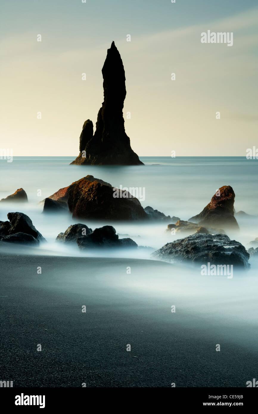 Wellen im ganzen schwarzen vulkanischen Felsnadeln entlang der Vik in Island Stockfoto