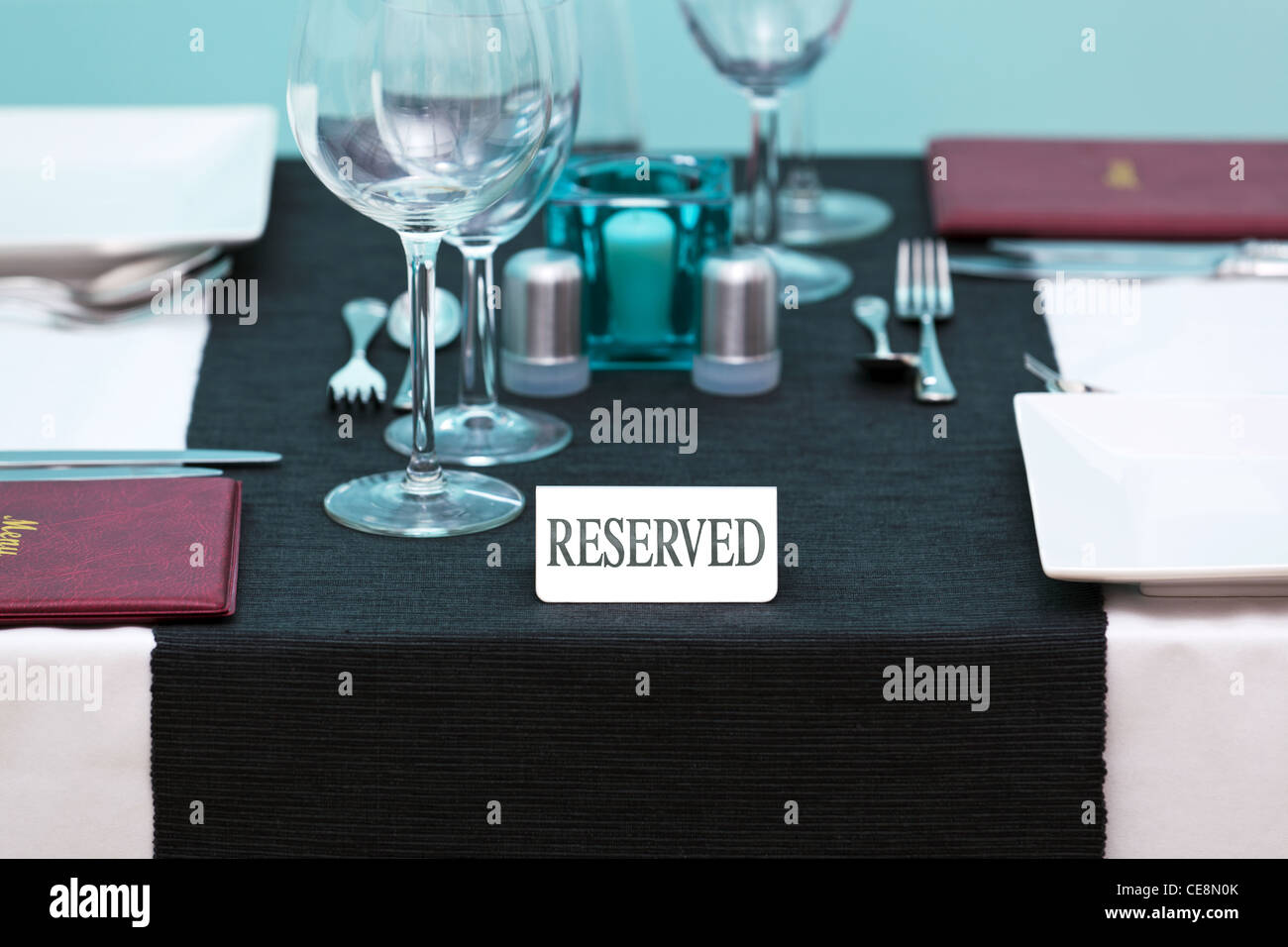 Foto von einem reserviert loggen Sie sich ein Tisch im Restaurant mit Menüs auf der Seite und Gedeck für Stockbild