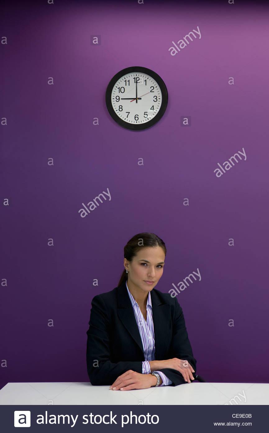 Porträt von Ernst Geschäftsfrau sitzen am Schreibtisch unter Uhr Stockbild