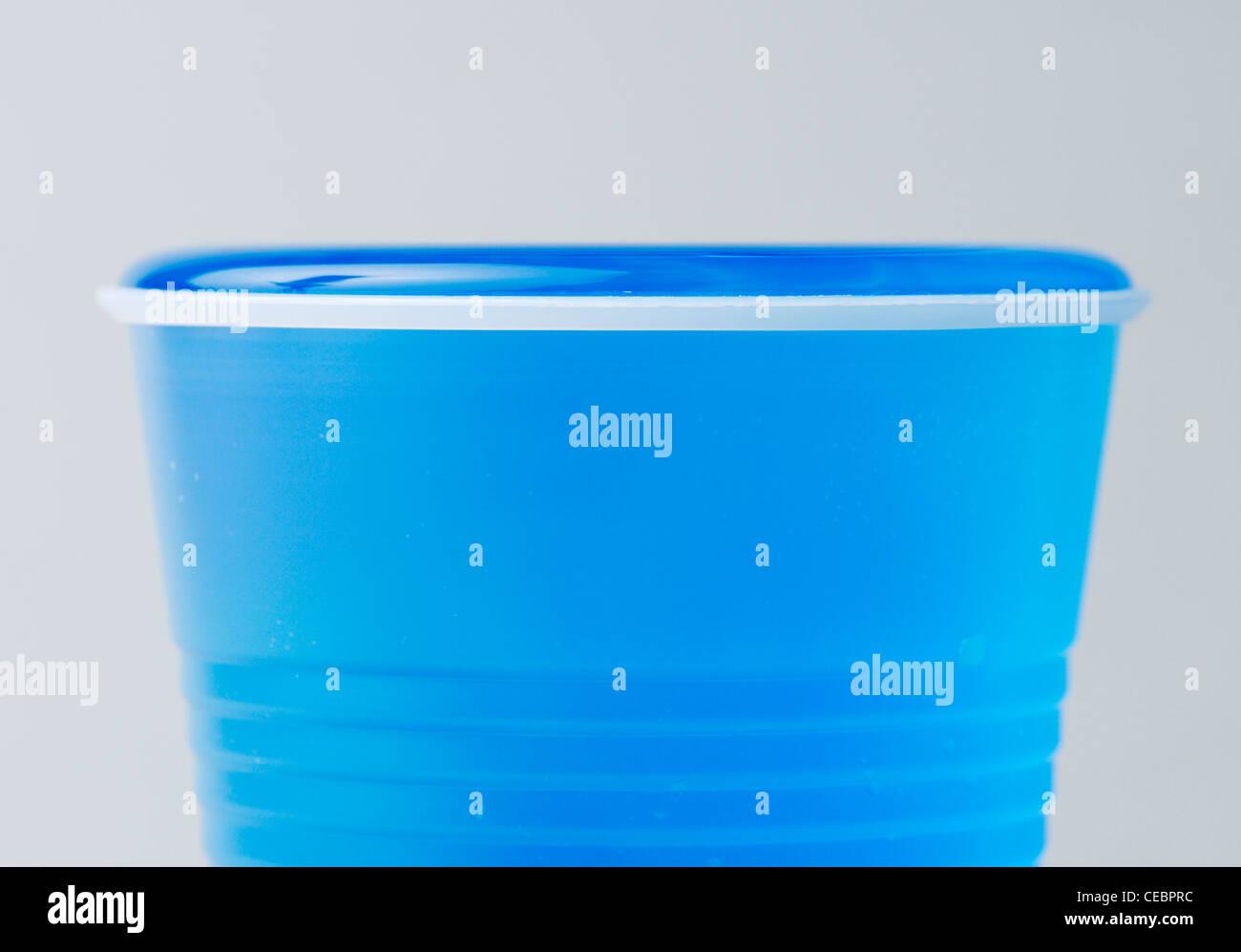 Wasser trotzt der Schwerkraft über den Rand einer Tasse Oberflächenspannung durch Zusammenhalt zwischen Stockbild