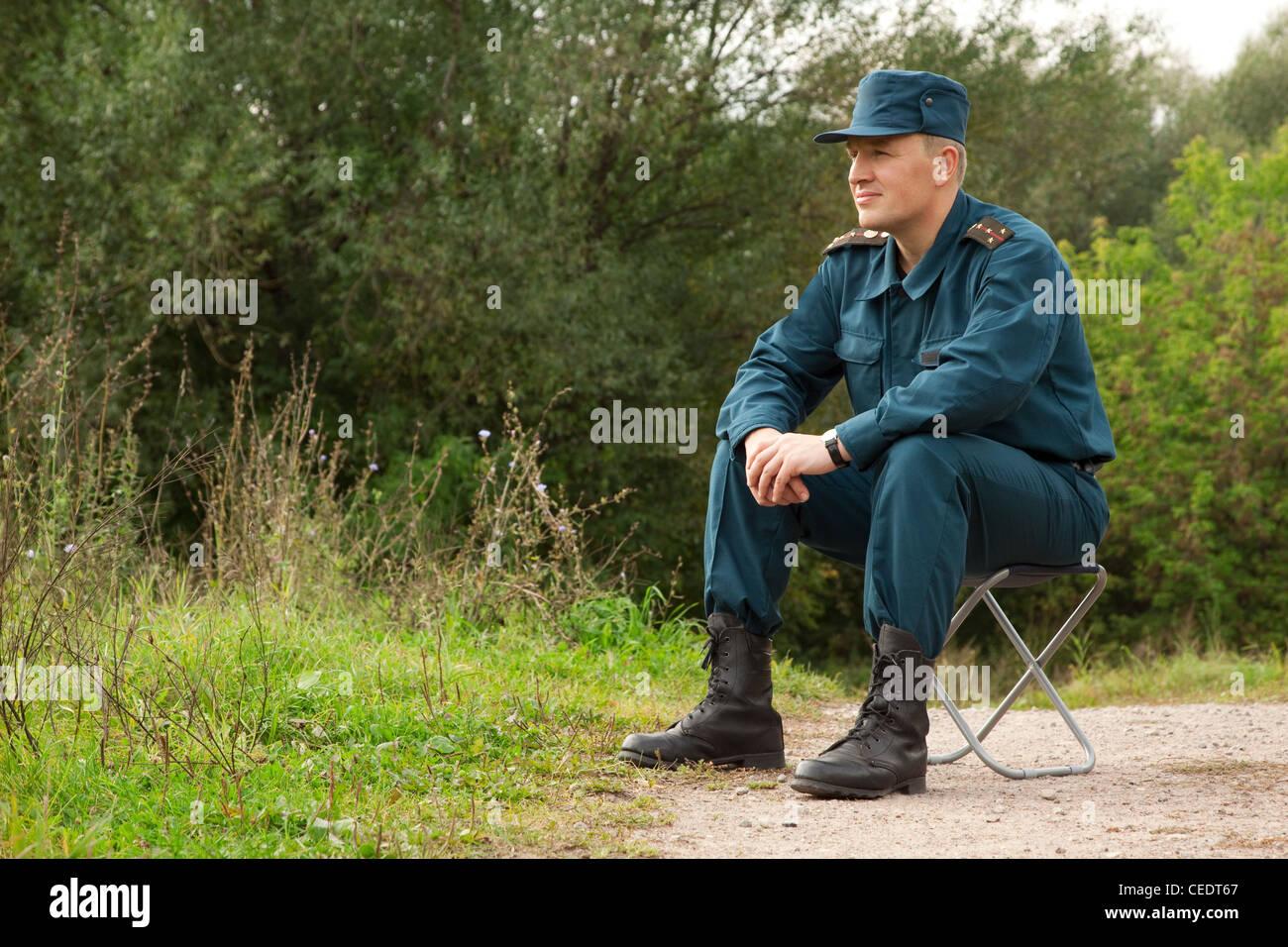 militärische Mann sitzt auf dem Camp-Stuhl im freien Stockbild
