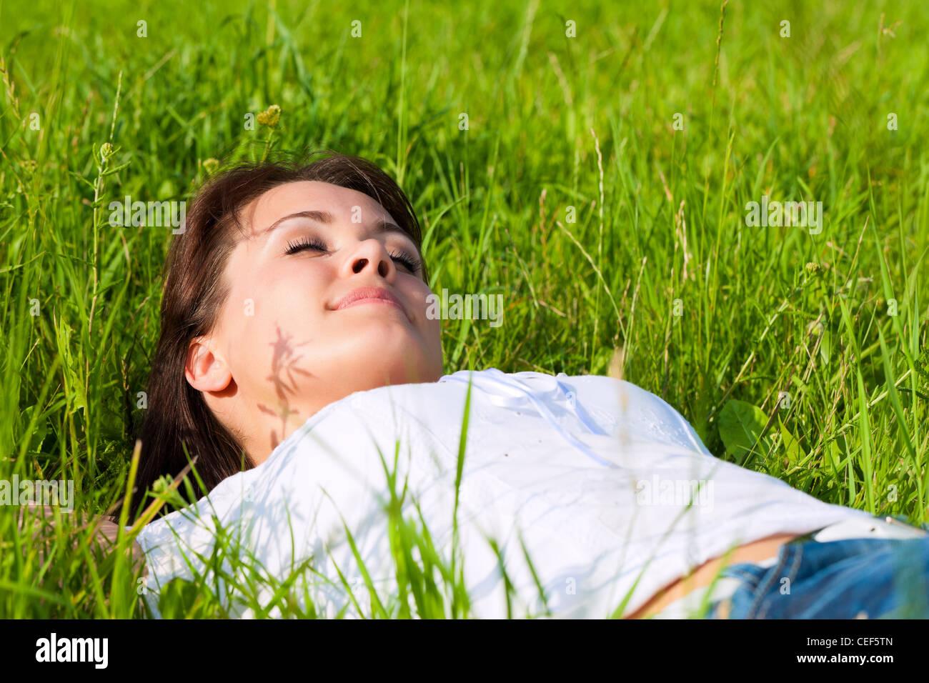 Junge Frau, die Verlegung auf einem Rasen oder Wiese im Sommer träumen und schlafen Stockbild