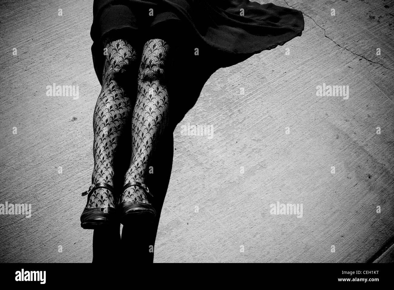 Frau trägt Strumpfhosen, Verlegung auf Asphalt. Schwarz und weiß. Stockbild