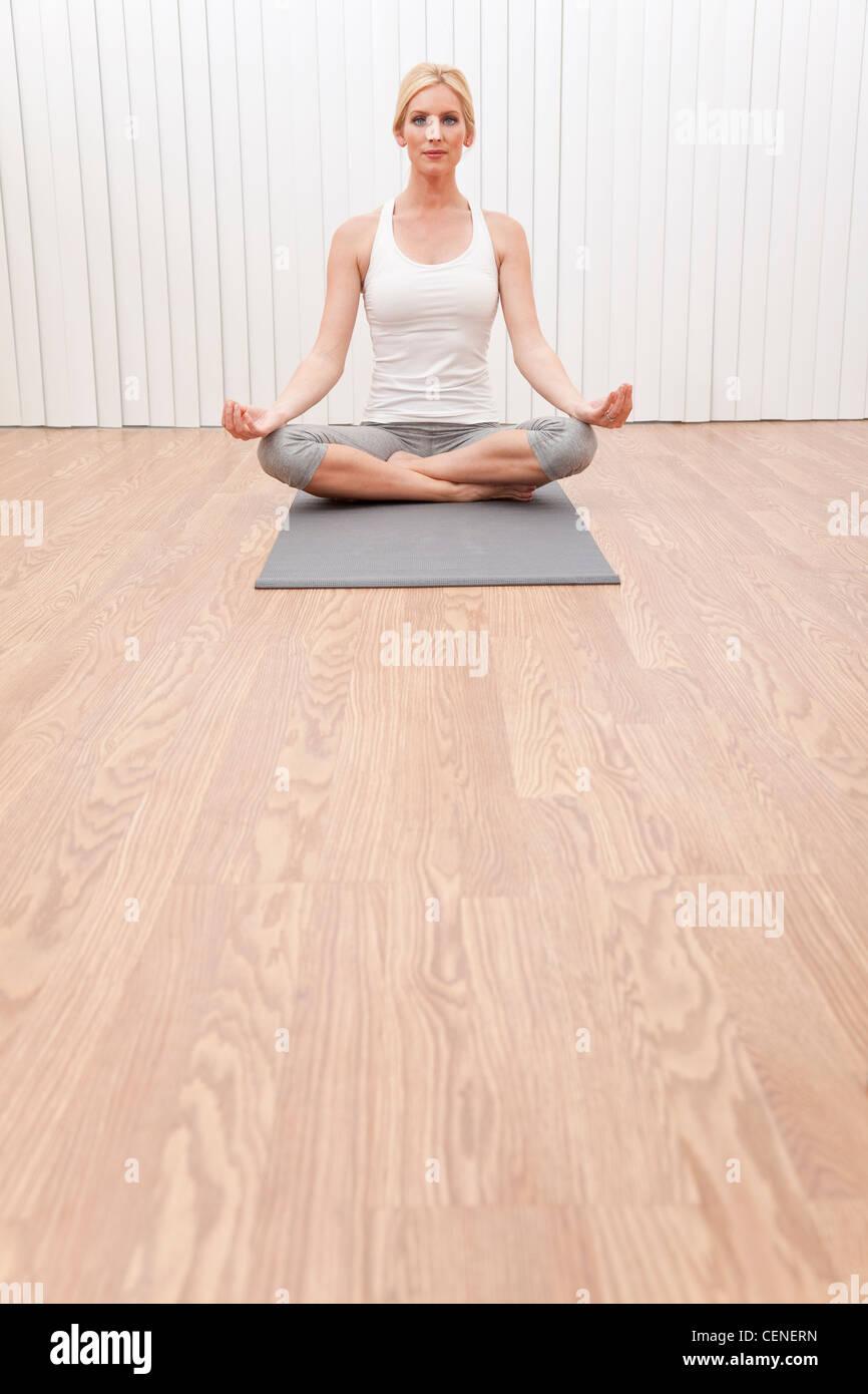 Eine schöne junge blonde Frau Schneidersitz sitzen in einer Yogaposition in einem Fitnessstudio Stockbild