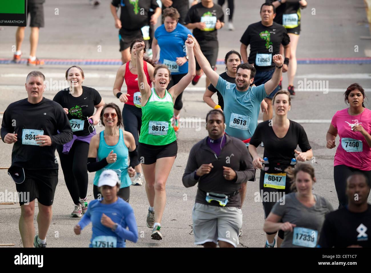 Sportler zu feiern, als mehr als 18.000 Läufer die Straßen der Innenstadt von Austin für das jährliche Stockbild
