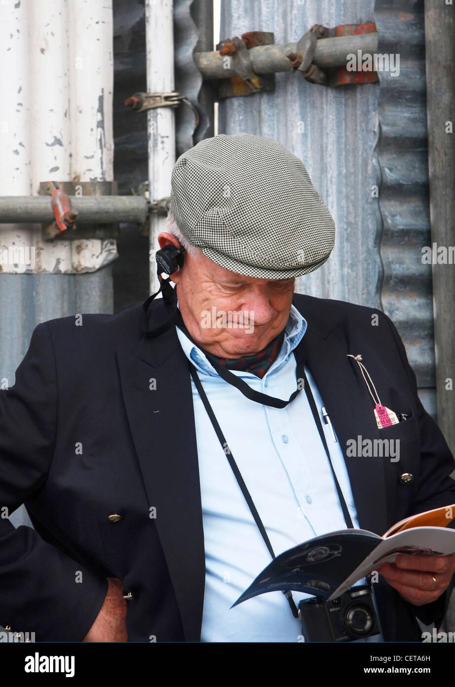 Mann liest Rennkalender beim Goodwood Revival. Stockbild