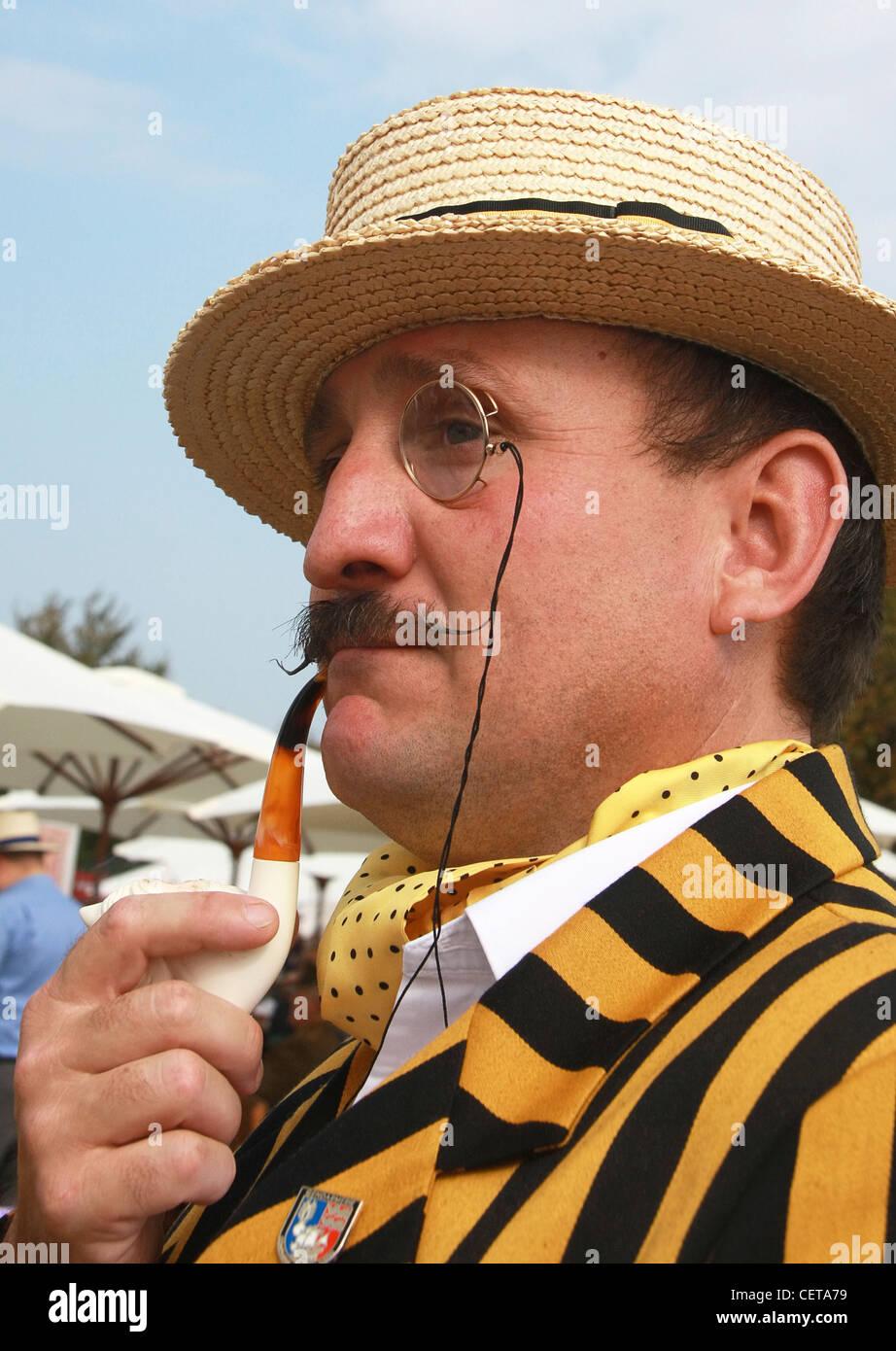 Mann mit Monokel, Strohhut und Pfeife beim Goodwood Revival. Stockbild