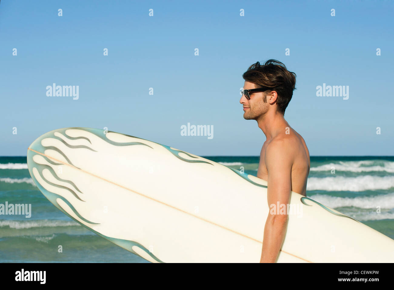 Mann mit Surfbrett am Strand Stockbild