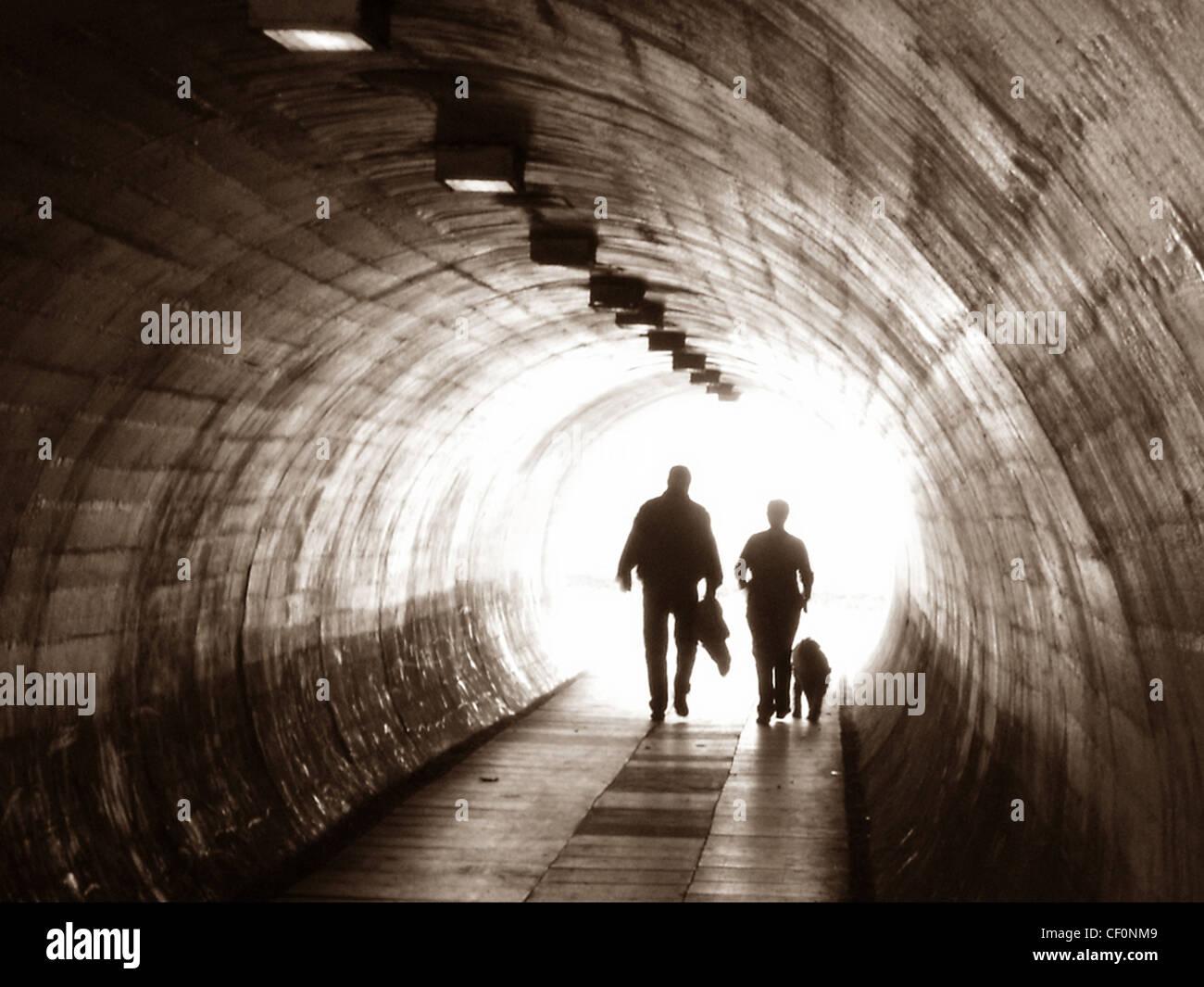 Laden Sie dieses Alamy Stockfoto Zwei Personen und einem Hund zu Fuß durch einen Tunnel am Latchford (aus Kingsway), Warrington, Cheshire, England, UK - CF0NM9