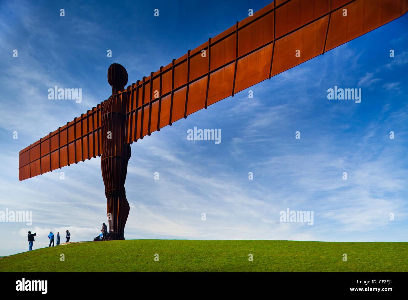 """Touristen stehen unter der Ikone Engel der nördlichen Statue von Antony Gormley. Der """"Engel"""", gebaut Stockbild"""