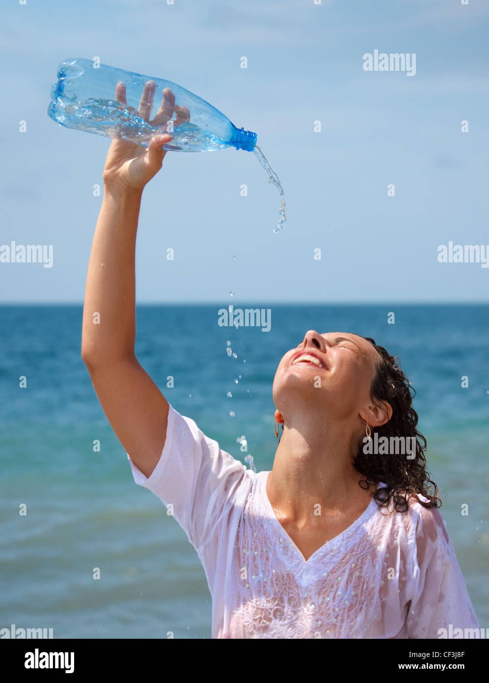 Mädchen-Spritzwasser über sich selbst aus der Flasche, heißen sonnigen Tag am Strand. Stockbild